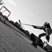 Roller hockey. Rollerhockey. Homme en train de marquer un but. Crosse de hockey.