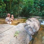 Baignade a Saul en foret tropicale amazonienne. Riviere. Crique. Sentier Roche bateau. En famille. Avec des enfants et bebe. Bain dans une crique sablonneuse.  Maman et sa fille. Tourisme.  Parc amazonien de Guyane.