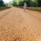 Village de Saul en Guyane. Pas sur le sol en latérite. Route. Petite fille, bebe, en train de marcher.