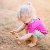 Petite fille en train de jouer avec de la terre et des cailloux. Bebe.