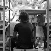"""Usine chinoise de fabrication de chaussures. Ouvrier sur chaine de production, de dos, assis sur un minuscule tabouret couche de cote. Chine, Shenzhen, usine du monde. Travail plus de 70 heures par semaine, a faible couts, pour utilisation des produits par les pays """"riches"""". Made in China. Derriere lui se trouve le reste de la chaine de production avec les ouvriers."""