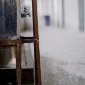 """Dortoirs d'une usine chinoise de fabrication de chaussures. Chaque dortoir d'environ 25 metres carres comporte 12 lits (superposes) pour les ouvriers de l'usine. Les ouvriers passent une quinzaine d'annee dans les usines en ville, en envoyant le peu d'argent qu'ils gagnent dans leurs familles (enfants, parents) restes dans les campagnes.  L'eau est disponible a l'exterieur des dortoirs uniquement par cette reserve et le robinet sur la photo.    OuvriËres ‡ la chaÓne, couturiËres sur machines ‡ coudre. Chine, Shenzhen, usine du monde. Travail plus de 70 heures par semaine, ‡ faible co˚ts, pour utilisation des produits par les pays """"riches""""."""