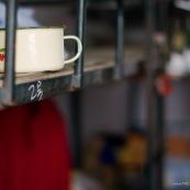 """Dortoirs d'une usine chinoise de fabrication de chaussures. Chaque dortoir d'environ 25 metres carres comporte 12 lits (superposes) pour les ouvriers de l'usine. Les ouvriers passent une quinzaine d'annee dans les usines en ville, en envoyant le peu d'argent qu'ils gagnent dans leurs familles (enfants, parents) restes dans les campagnes.  Le lit est l'unique zone privee des ouvriers, sur lesquels ils gardent le peu d'objets qu'ils possedent. La tasse pour boire le the est l'element incoutournable. Ici sur un des lits superposes.     OuvriËres ‡ la chaÓne, couturiËres sur machines ‡ coudre. Chine, Shenzhen, usine du monde. Travail plus de 70 heures par semaine, ‡ faible co˚ts, pour utilisation des produits par les pays """"riches""""."""