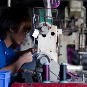 Usine en Chine. Ouvrier en train de faire de la couture sur machine a coudre.