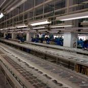 """Usine chinoise de fabrication de chaussures et autres produits (protections, sacs...). Ouvriers a la chaine, en train de realiser des serigraphies. Chine, Shenzhen, usine du monde. Travail plus de 70 heures par semaine, a faible couts, pour utilisation des produits par les pays """"riches""""."""