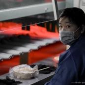 Ouvriere chinoise dans une usine en Chine. Process chaussure. Devant un four ou seche la colle.