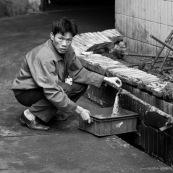 Ouvrier chinois prenant de l'eau dans une usine de fabrication de pièces métalliques. Made in china. Conditions de travail difficiles, conditions précaires. L'ouvrier est accroupi à même le sol. Usine en Chine.  Noir et blanc.