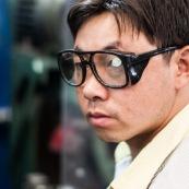 Ouvrier chinois dnas une usine en Chine avec des lunettes de protection. Il n'a pas enlevé le sticker des lunettes !