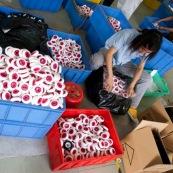 """Usine chinoise de fabrication de roues en polyurethanes (pour valises, roues de skateboards, rollers...). Chine, Shenzhen, usine du monde. Travail plus de 70 heures par semaine, a faible couts, pour utilisation des produits par les pays """"riches"""", dans des conditions de travail Èpouvantables. Ouvriers a terre en train de trier des roues."""
