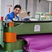 Usne en Chine. Ouvrier en train de decouper des tissus.
