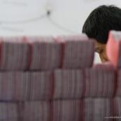 Usine en Chine. Ouvrier derriere sa pile de produits.