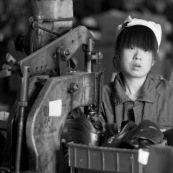 """Ouvriere chinoise sur machine a riveter dans une usine de fabrication de chaussures en Chine. Made in china. Conditions de travail difficiles plus de 70 heures par semaine, pour fabriquer les produits utilises par les pays """"riches"""". Le cout de la main d'oeuvre y est tres faible. Assemblage de rollers."""
