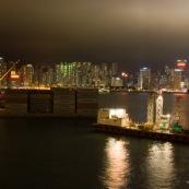"""Depuis Kowloon ‡ Hong-Kong, vue sur Central, et sur des containers qui doivent partir par bateau en direction des pays occidentaux. Vue de nuit. transport maritime de marchandises """"made in China""""."""