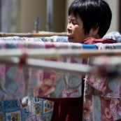 A hong-kong en Chine, femme en train d'etendre son linge dans la rue.