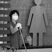 A hong-kong en Chine, femme devant les toilettes en train d'attendre pour faire le menage.