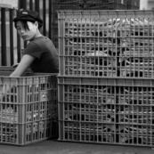 Ouvrière chinoise triant des produits dans une usine de fabrication de pièces métalliques. Made in china. Conditions de travail difficiles, conditions précaires. L'ouvrière est accroupie à même le sol. Noir et blanc.